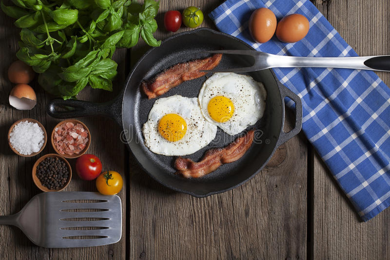 Bacon and Eggs Iron Skillet. Fried bacon and eggs in cast iron skillet set on rustic wood table with fresh herbs, tomatoes and spices royalty free stock images