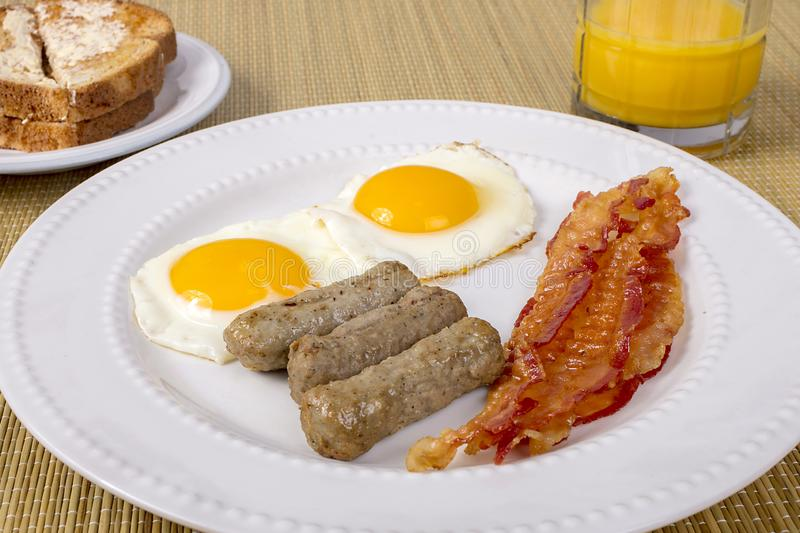 Bacon, Eggs And Sausage. Breakfast on a white plate stock images