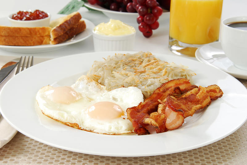 Bacon eggs and toast. Breakfast of bacon, eggs, hash browns and toast royalty free stock image