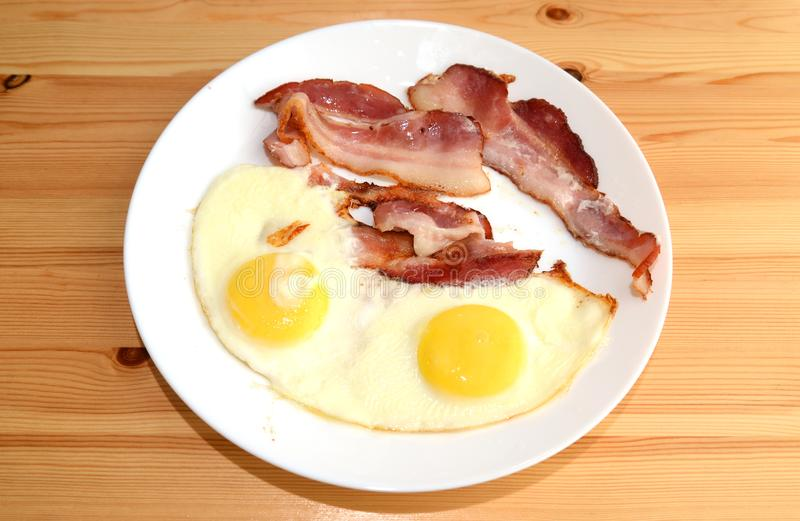 Bacon and eggs. Bacon and eggs on a white plate on a wooden background royalty free stock images