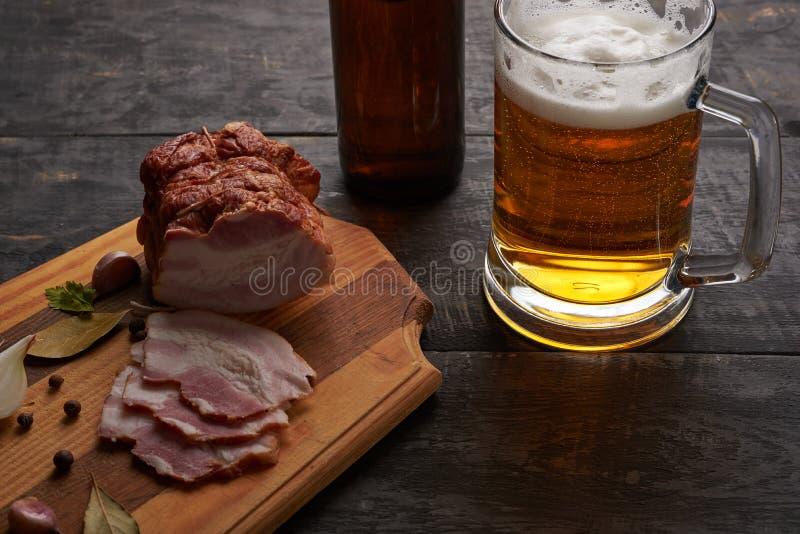 Bacon en glas bier op een lijst stock foto