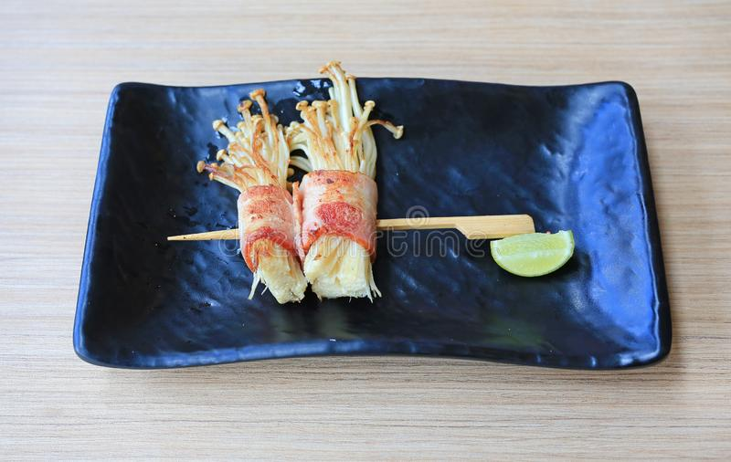 Bacon and Enoki Mushroom roll stick served with lemon on black plate on wood table. Japanese cuisine food royalty free stock photo