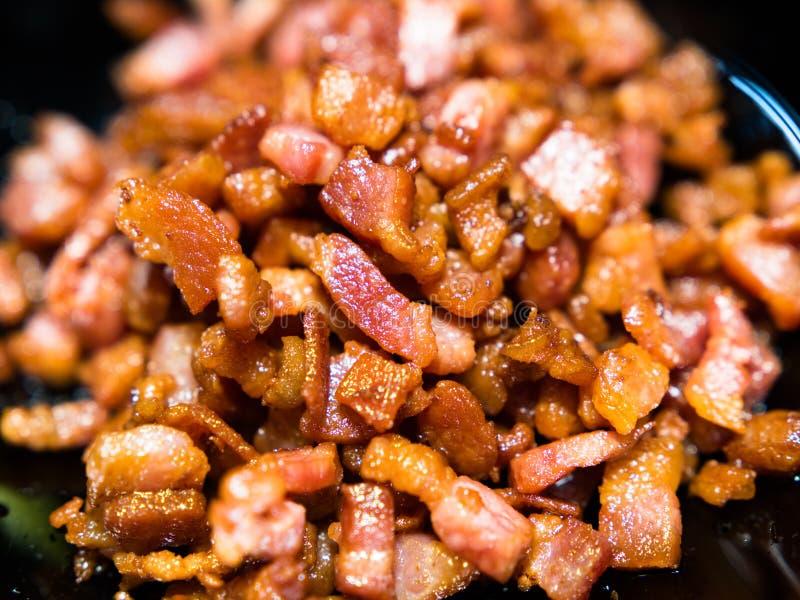 Bacon fritto tagliato e croccante su fondo nero fotografia stock libera da diritti