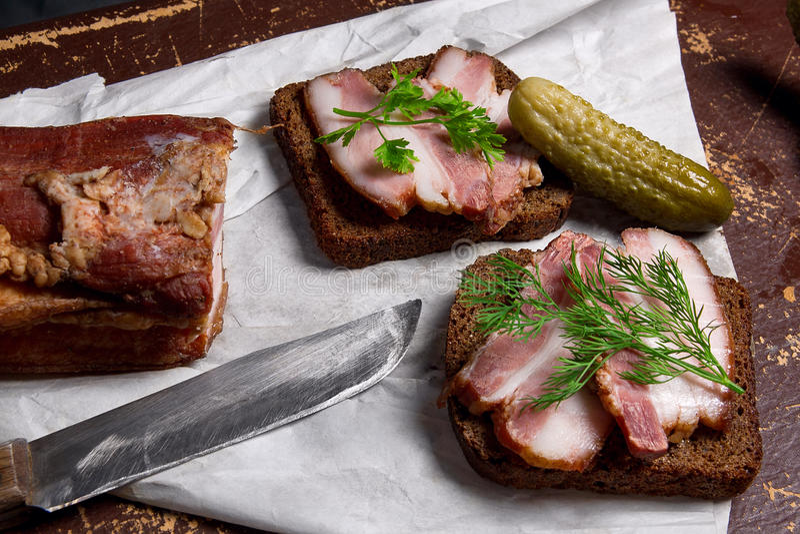 Bacon fumado com pão preto do centeio e diversas salmouras no pac fotografia de stock
