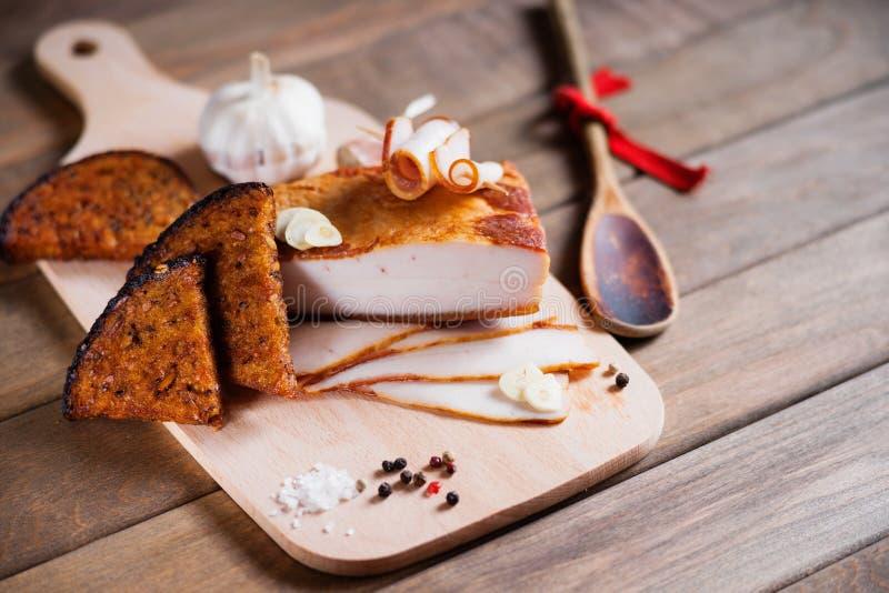 Bacon fumado e pão cortado em uma placa de corte de madeira fotografia de stock