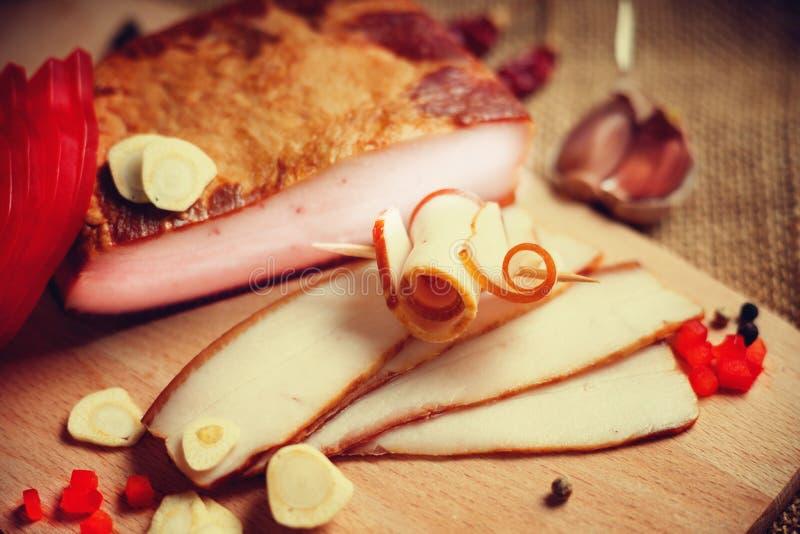 Bacon fumado em uma placa de corte de madeira imagens de stock