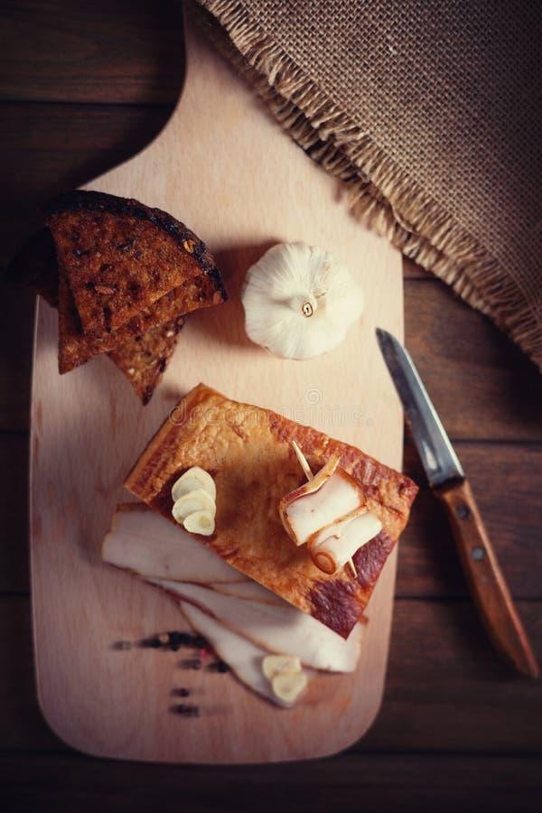 Bacon fumado, faca e pão cortado em uma placa de corte de madeira fotografia de stock