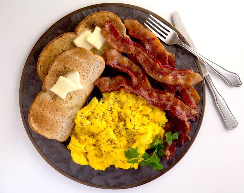 Bacon, gespleten eieren en toast op blik stock fotografie