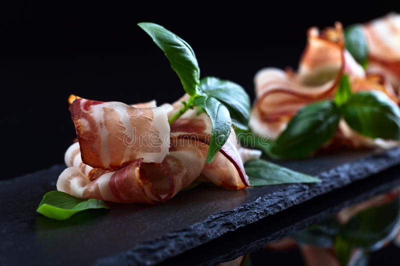 Bacon with green basil royalty free stock photography
