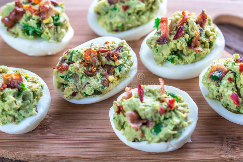 Bacon guacamole deviled eggs. On the wooden board stock photography