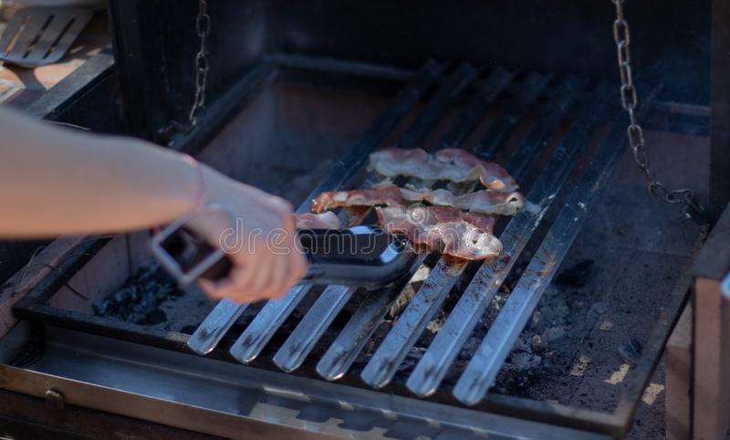 Bacon het koken op de houtskoolbarbecue die met handen een paar tang houden royalty-vrije stock afbeelding
