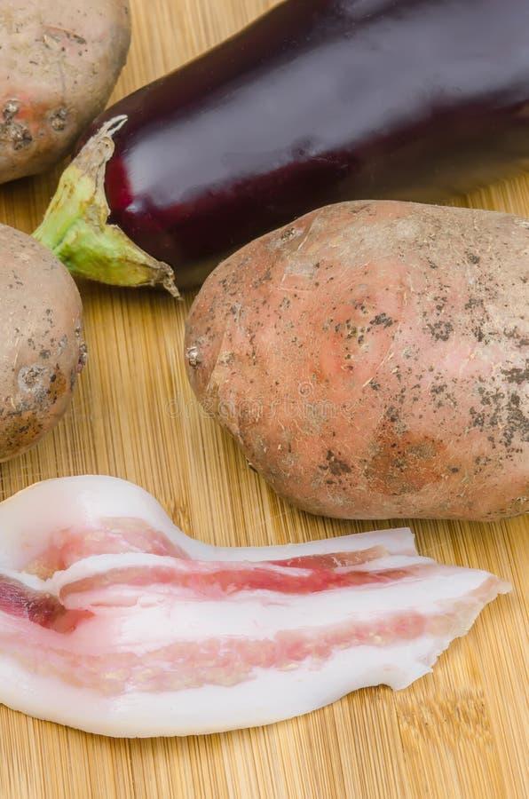 Bacon met verse aubergine en aardappels stock afbeeldingen