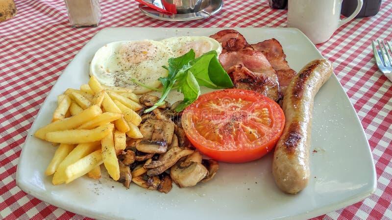Bacon och ägg frukosterar med tomaten, korven, chiper och champinjoner royaltyfria foton