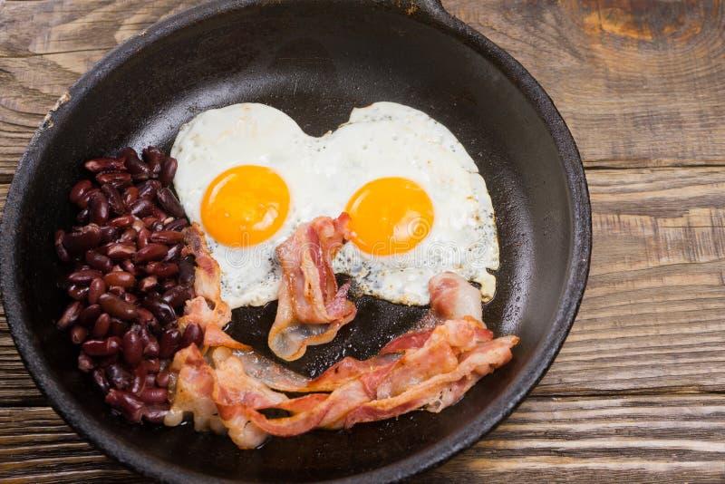 Bacon, ovo e feijão Ovo salgado e polvilhado com a pimenta preta O café da manhã inglês grelhou o bacon, dois ovos e os feijões n imagens de stock royalty free