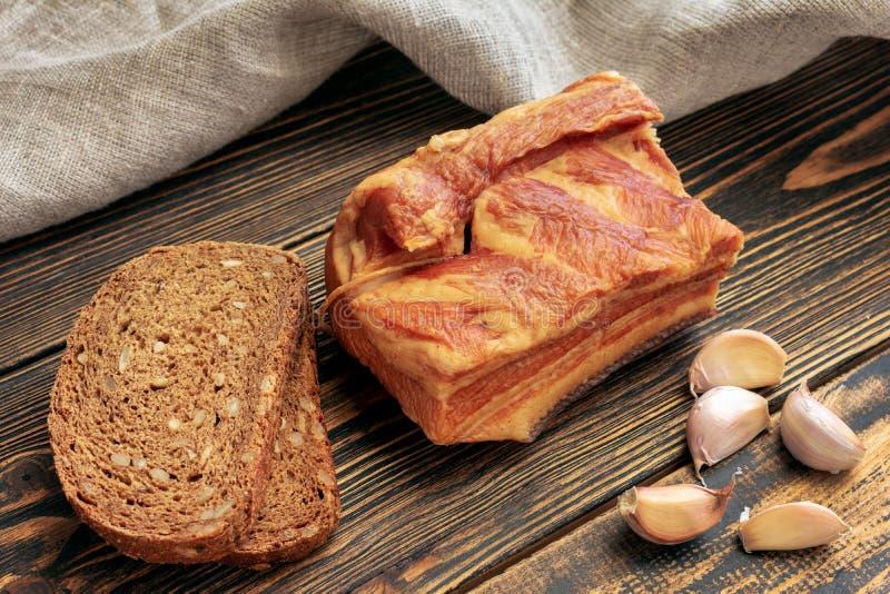 Bacon, pane di segale ed aglio fumati su fondo di legno fotografia stock libera da diritti