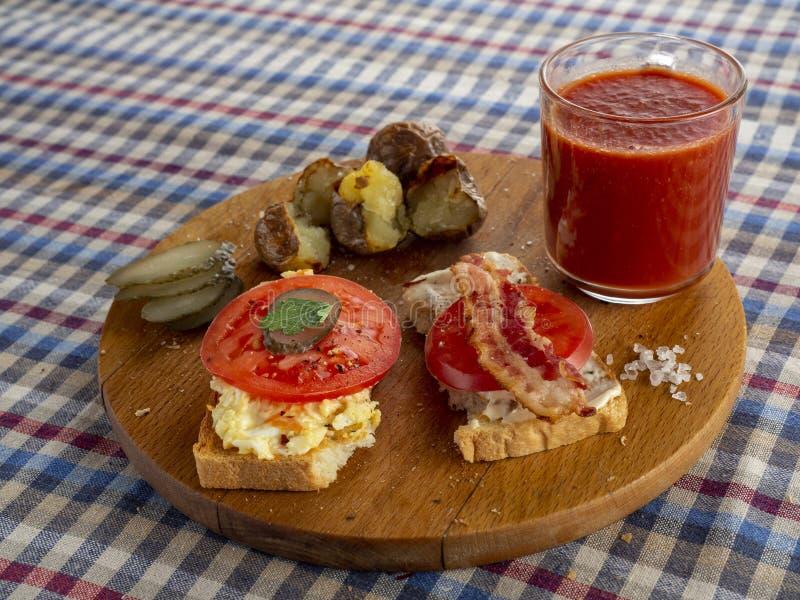 Bacon sandwich, fried tomato and tomato juice. Cowboy style stock image