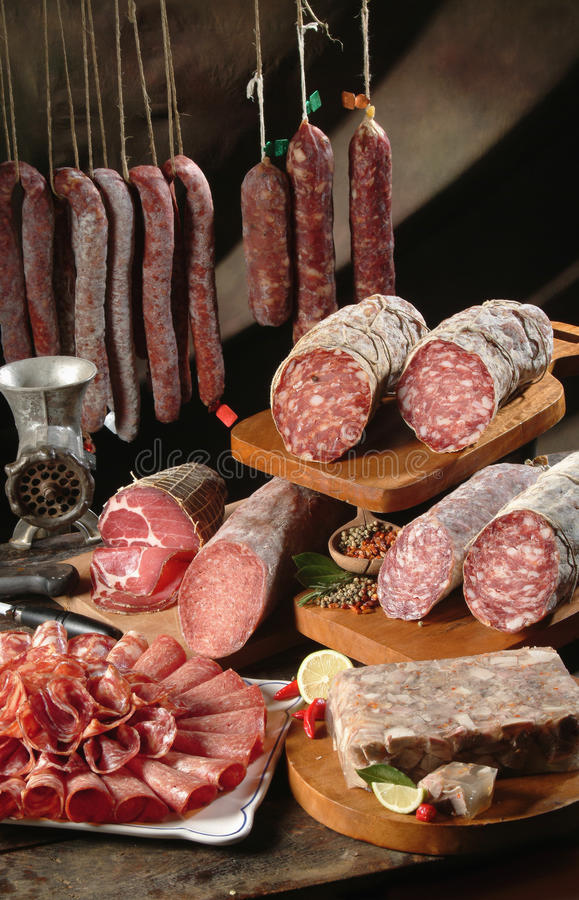 Bacon sausage and salami. A classic still life of bacon, salami, sausage and pork gelatin on an old table stock images