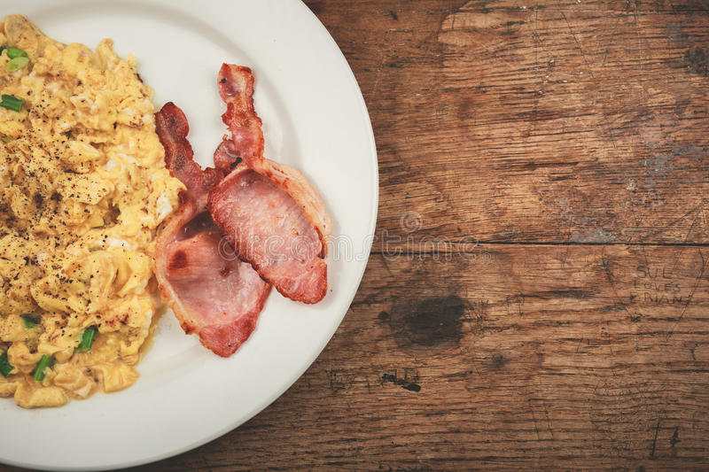 Bacon and scrambled eggs. On a white plate stock photos