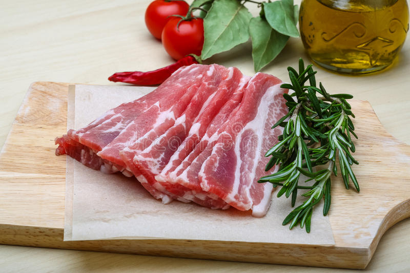 Bacon. Sliced bacon with rosemary on the wood background royalty free stock photo
