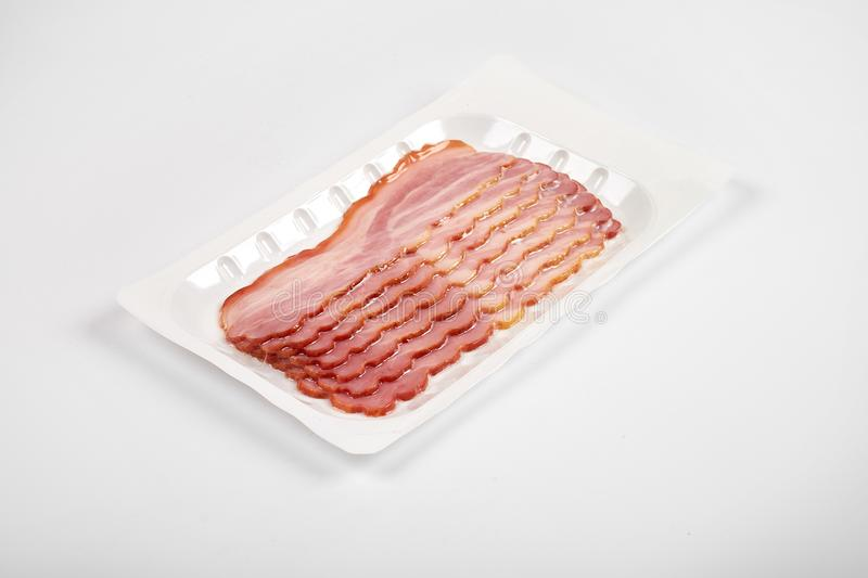 Bacon slices on the package, isolated on white background royalty free stock images