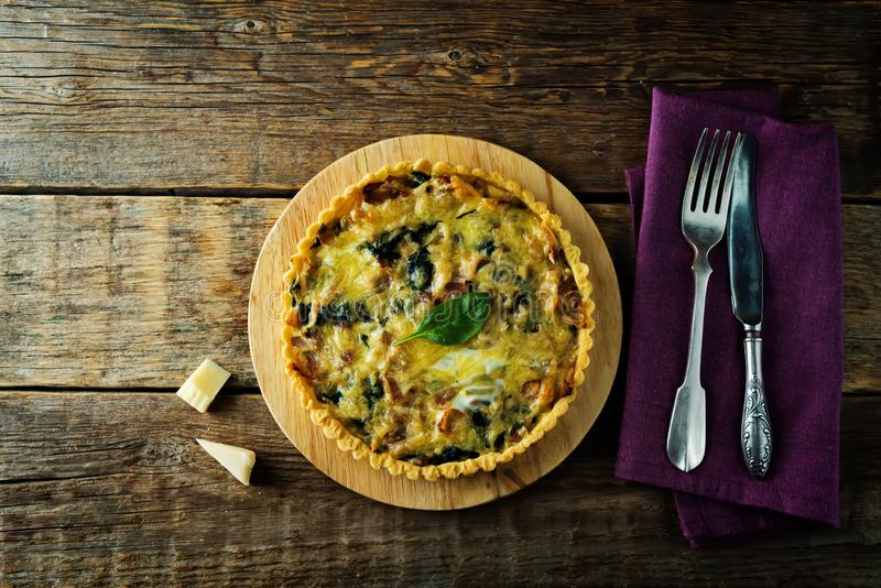 Bacon spinach quiche with fresh spinach leaves royalty free stock photos