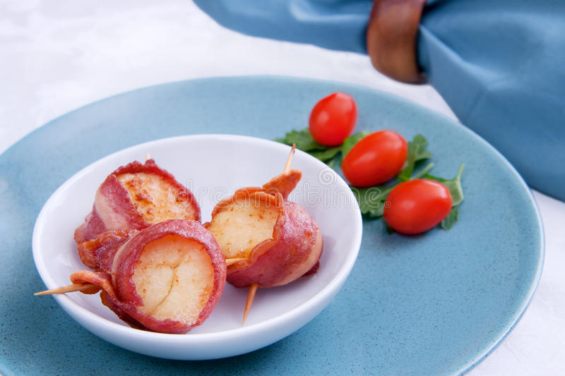 Bacon wrap scallops. Three delicious bacon wrapped scallops in a white bowl with tomato and oregano garnish on a blue plate stock photo