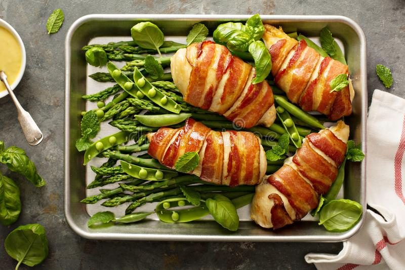 Bacon wrapped chicken breast with asparagus stock photos