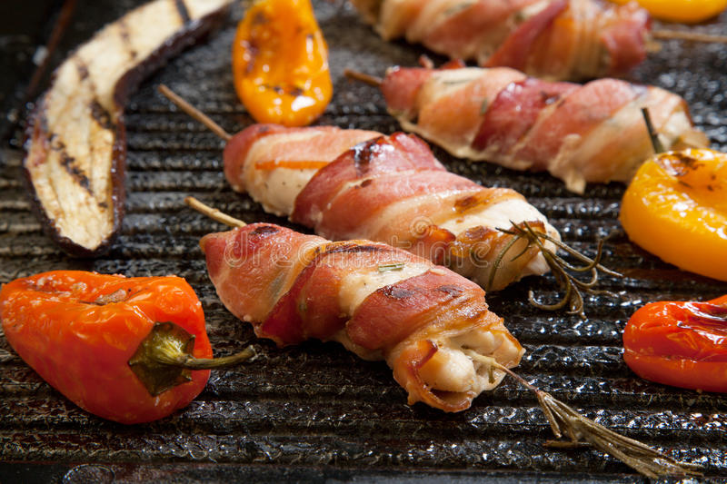 Bacon-Wrapped Chicken Tenders. Grilled bacon-wrapped chicken tenders with lemon and rosemary on the grill wih grilled vegetables - peppers, and and eggplant stock photos