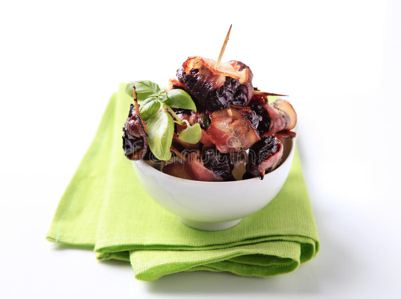 Bacon wrapped prunes stock image