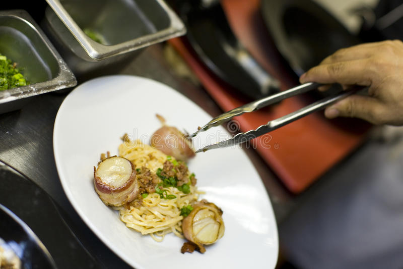 Bacon wrapped scallops and Fettuccine. Being prepared in the kitchen at a restaurant royalty free stock images