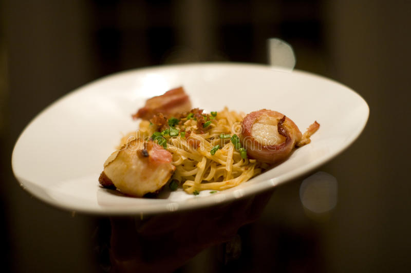 Bacon wrapped scallops and Fettuccine. Being served at an upscale restaurant royalty free stock photo
