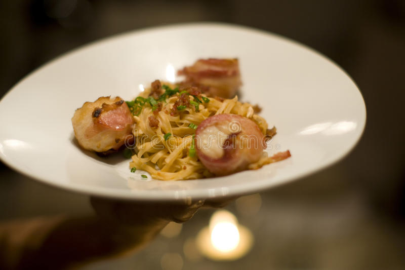 Bacon wrapped scallops and Fettuccine. On a plate being served royalty free stock photography