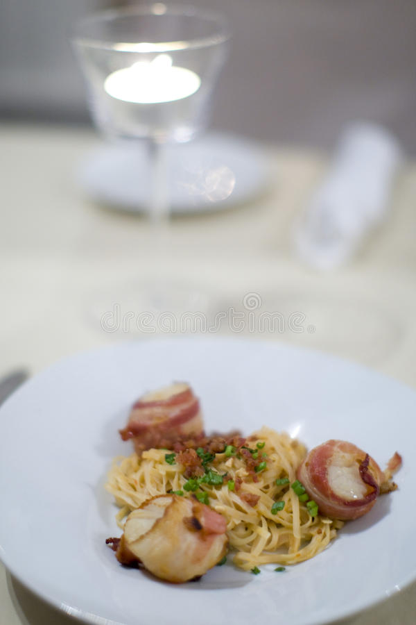 Bacon wrapped scallops and Fettuccine. At upscale restaurant royalty free stock images