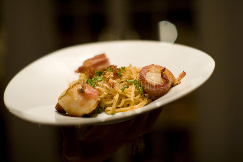 Bacon wrapped scallops and Fettuccine on a white plate. Bacon wrapped scallops and Fettuccine at a restaurant on a plate royalty free stock image