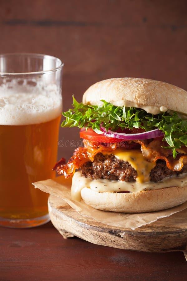 Baconosthamburgare med öl för lök för tomat för nötköttliten pastej arkivfoton