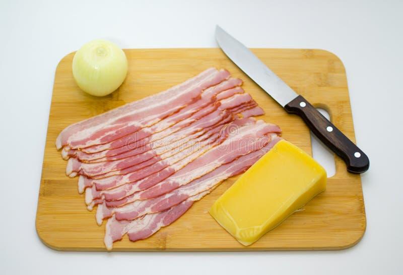 Baconplakken, Parmezaanse kaaskaas, ui op het Hakbord E royalty-vrije stock afbeelding