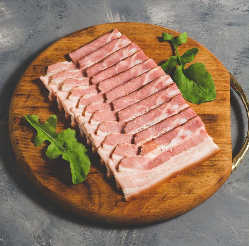 Baconskivor som skivas på en skärbrädanärbild tonat foto royaltyfri foto