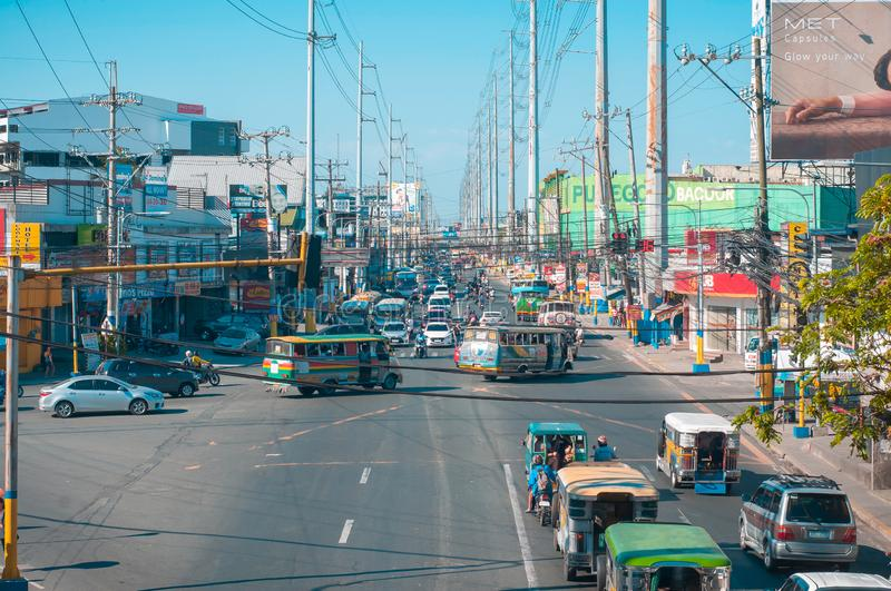 Sunny weather in a busy city of Bacoor, Cavite Philippines. Bacoor, Cavite, Philippines - April 2019 - nUrban roads with electricity poles on road sides, row of royalty free stock image