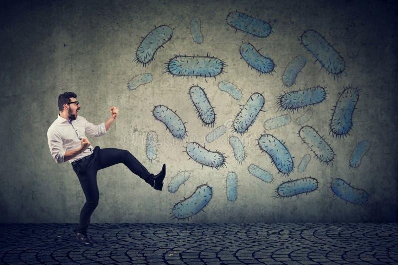 Bactérias de combate do homem seguro irritado imagens de stock