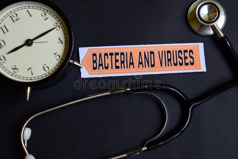 Bacteria and Viruses on the paper with Healthcare Concept Inspiration. alarm clock, Black stethoscope. stock image