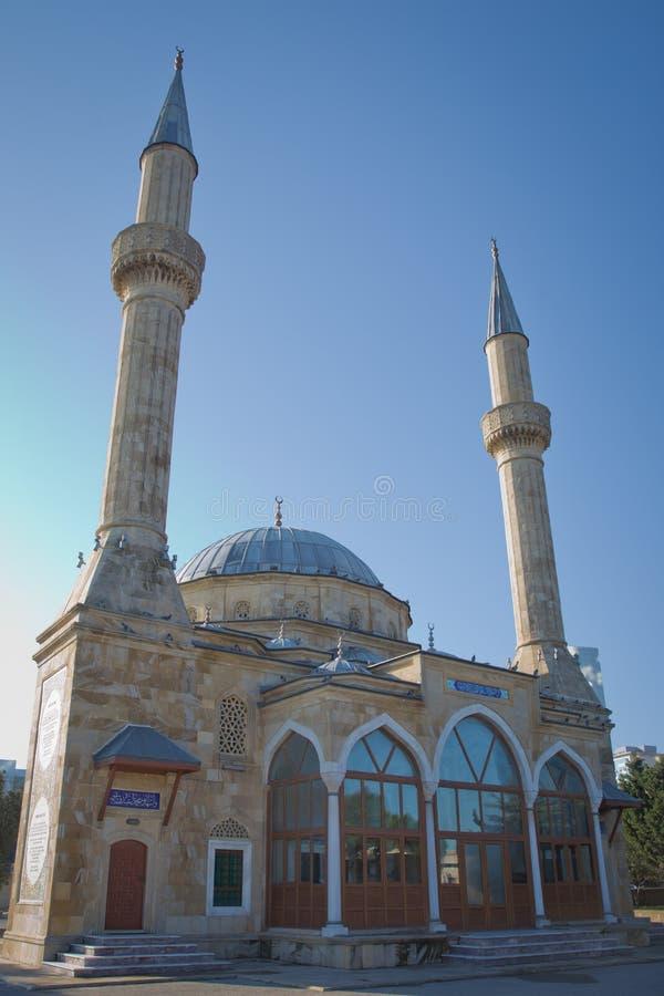 BACU, AZERBAIGIAN: La moschea della moschea di Sehidler Mescidi dei martiri, moschea turca con la fiamma si eleva grattacielo den fotografie stock libere da diritti