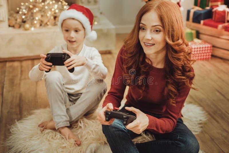 Baczna kobieta bawić się gra wideo z synem zdjęcie stock