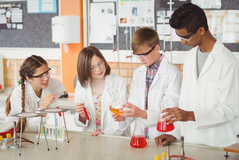 Baczni szkolni dzieciaki robi chemicznemu eksperymentowi w laboratorium fotografia stock