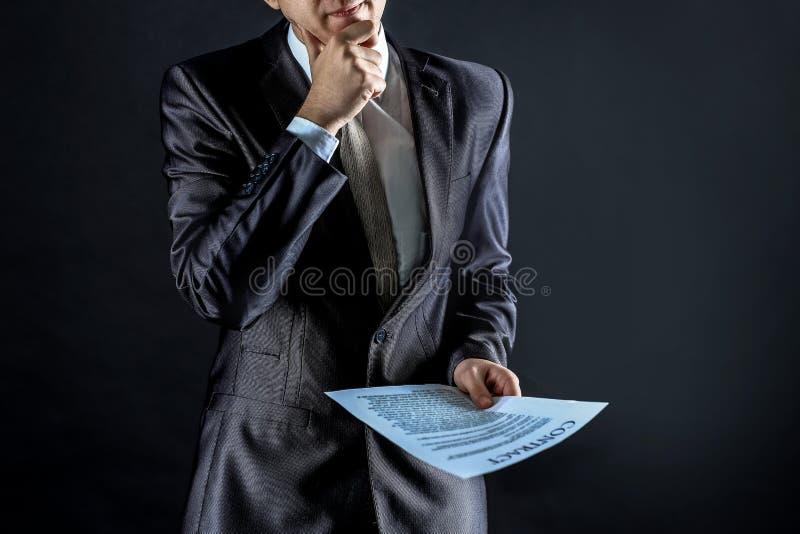 Baczny biznesmen jest bior?c pod uwag? terminy nowy kontrakt zdjęcie stock