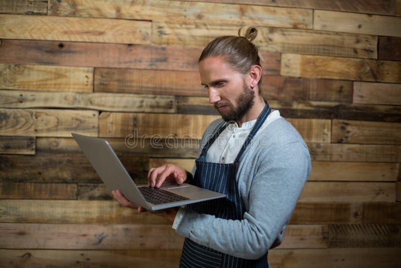Baczny kelner używa laptop przeciw drewnianej ścianie obrazy royalty free