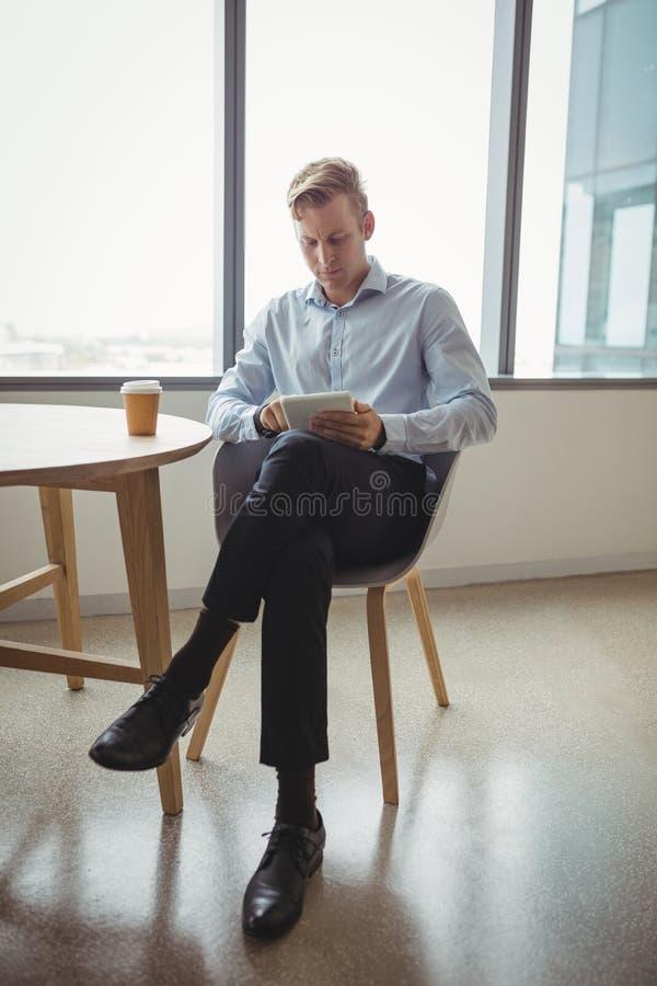 Baczny kierownictwo używa cyfrową pastylkę przy stołem fotografia royalty free