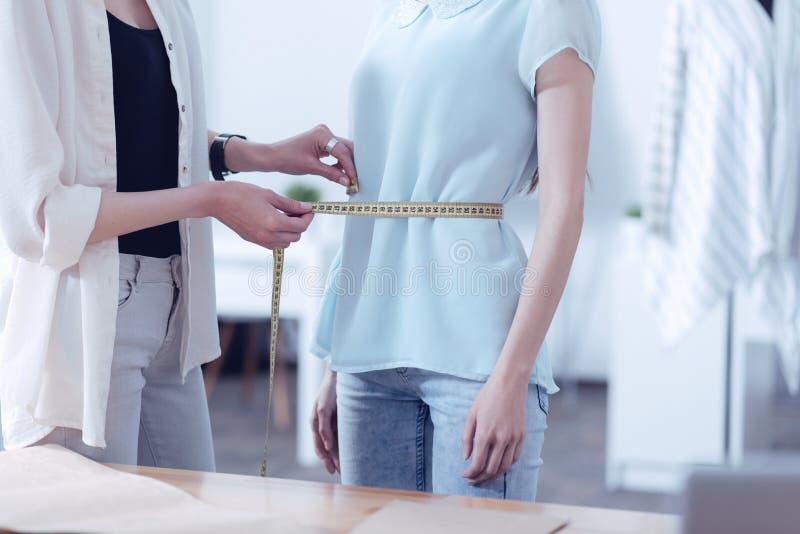 Baczny krawczyna mierzy talię jej klient obraz stock