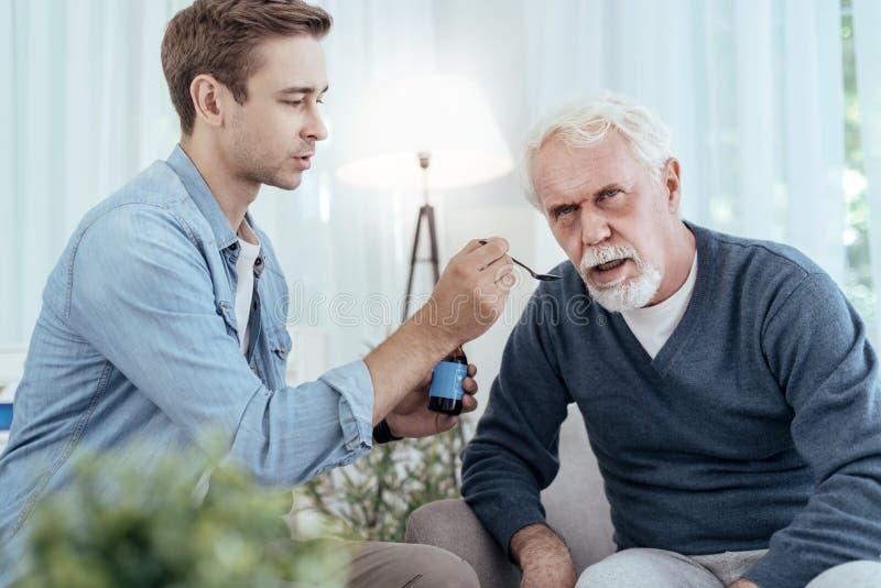 Baczny mężczyzna daje lekowi starszy mężczyzna zdjęcie stock
