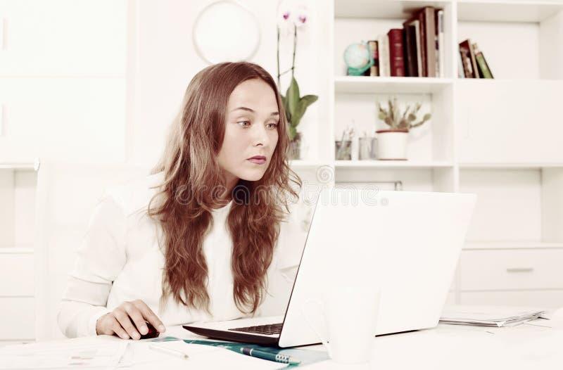 Baczny młody żeński działanie na laptopie w biurze zdjęcie royalty free