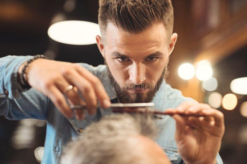 Baczny młody fryzjer męski pracuje w zakładzie fryzjerskim obraz royalty free